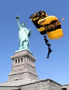 Two members of the Golden Knights, the U.S. Army's official parachute demonstration team, float through the air as part of a historical jump onto the grounds of the Statue of Liberty in New York City. The jump is part of the celebration of the Golden Knights 50th Anniversary. (Photo by Courtesy photo)